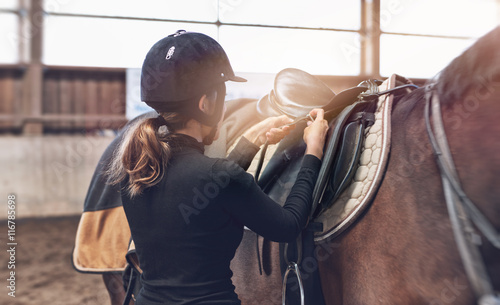 Woman rider adjusting her stirrups on her saddle