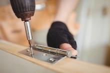 Carpenter Tightening Screw To Hinges On A Wooden Door