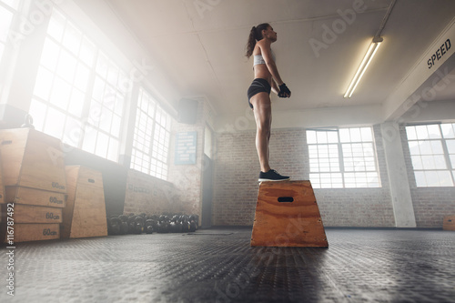 Photo  Fit young female standing on a box at gym