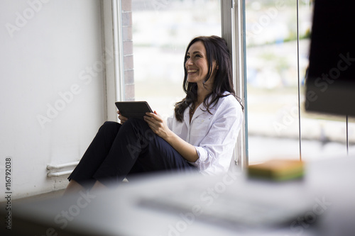 Businesswoman working barefoot on floor