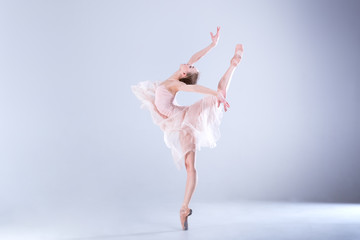 Ballet Perfection. Young and beautiful ballerina in a white dress is posing in a white studio full of light.
