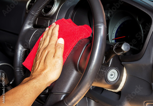 Hand with microfiber cleaning a car steering wheel