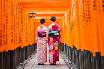 FototapetaTwo geishas among red wooden Tori Gate at Fushimi Inari Shrine in Kyoto, Japan. Selective focus on women wearing traditional japanese kimono.