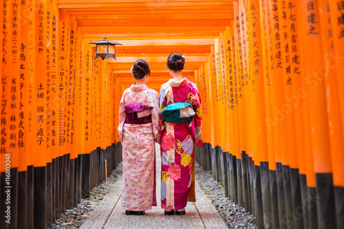 Two geishas among red wooden Tori Gate at Fushimi Inari Shrine in Kyoto, Japan. Selective focus on women wearing traditional japanese kimono.