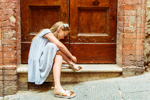 56bfd1817 Outdoor fashion portrait of a cute little girl wearing black and white dress  and golden sandals