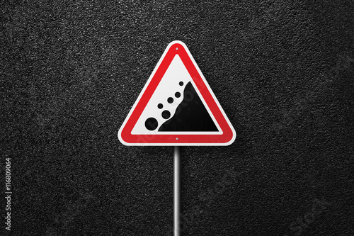 Fototapeta  Road sign triangular shape with a picture of the rockfall on a background of asphalt