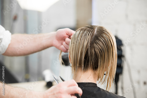 Fotografija  Hairdresser cutting client's hair in salon with electric razor closeup