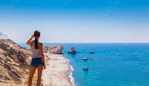Foto op Plexiglas Cyprus Woman looks on panoramic landscape Petra tou Romiou (The rock of the Greek), Aphrodite's legendary birthplace in Paphos, Cyprus island, Mediterranean Sea. Amazing blue green sea and sunny day.