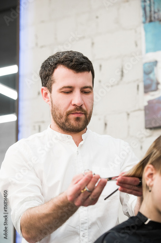 Fotografija  Male hairdresser making haircut for a client in professional hairdressing salon