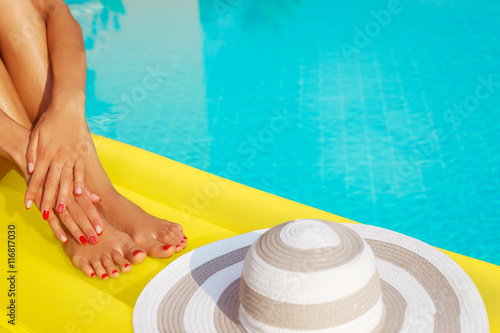 Poster Pedicure Portrait of beautiful tanned woman relaxing in swimming pool. Hat and inflatable matress. Legs and hands close up. Creative gel polish red pedicure and manicure. Hot summer day, bright sunny light.