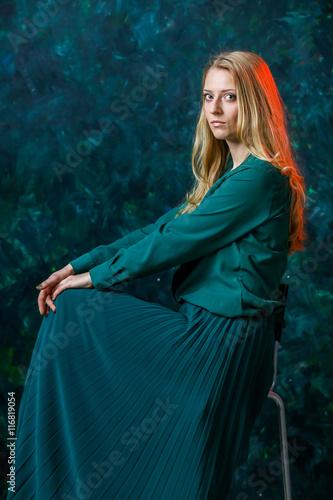 Fototapeta blonde girl on a green background in a long green dress obraz na płótnie