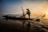 Rybak w akci w jeziorze, Tajlandia. idź ze swoją starą łodzią rybacką. - 116835224