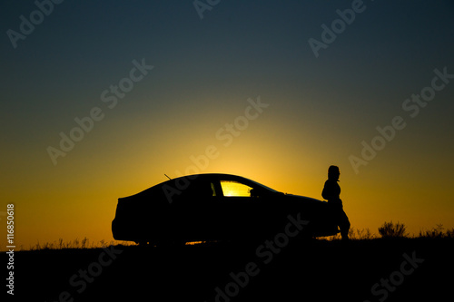Poster Old cars Silhouette of sedan car with girl on the background of beautiful sunset