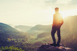 Leinwandbild Motiv Traveler young man standing in summer mountains at sunset and enjoying view of nature