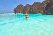 Young woman walks in turquoise clear waters of the Maya bay lagoon on the Ko Phi Phi Lee island