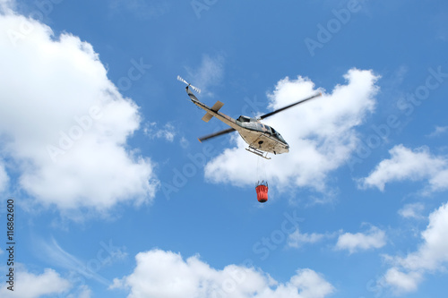 Firefighter helicopter flying with bambi bucket. плакат