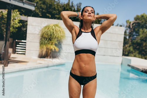Fit young woman in swimwear at the poolside Wallpaper Mural