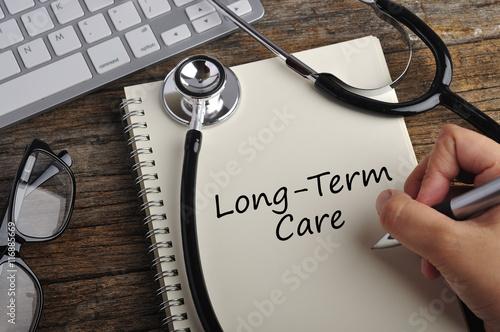 """Fényképezés  Women Hand Write """"LONG-TERM CARE"""" On Note Book"""