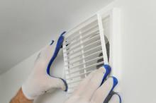 Worker Installs Ventilation Gr...