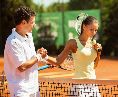 Young couple finish a tennis match.Shaking hands. - 116897846