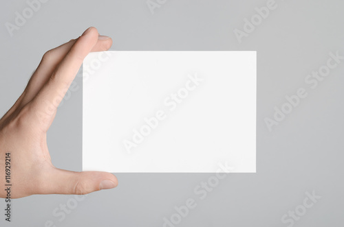 Fotomural A6 Flyer / Postcard / Invitation Mock-Up - Male hands holding a blank flyer on a gray background