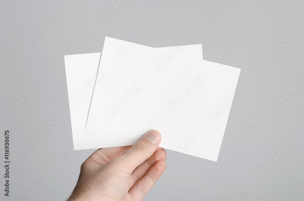 Fototapeta A6 Flyer / Postcard / Invitation Mock-Up - Male hands holding blank flyers on a gray background.