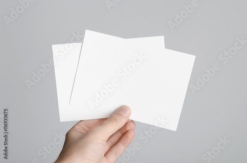 Fototapeta A6 Flyer / Postcard / Invitation Mock-Up - Male hands holding blank flyers on a gray background. obraz