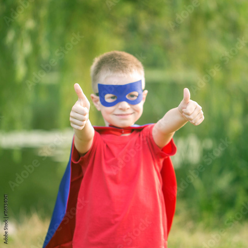 Fotografie, Obraz  Kid in super hero costume showing thumbs up.