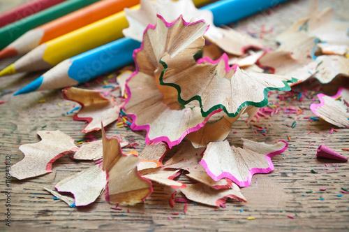 Taillures de crayons de couleur sur bureau décolier en vieux bois