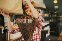 A Woman Pouring Coffee Beans Into A Grinder Hopper In A Coffee Shop.