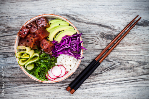Photo  Hawaiian tuna poke bowl with seaweed, avocado, red cabbage, radishes and black s