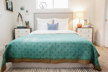 A Bedroom In An Apartment With A Double Bed And Beside Cabinets, And A Green Checked Patterned Bed Cover.