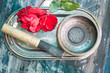 Tibetan singing bowl with stick and red rose petals on a silver tray