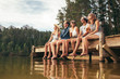 canvas print picture - Group of friends sitting on jetty at lake