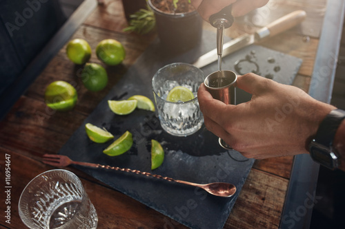 Fotomural Pouring alcohol in jigger to prepare a cocktail