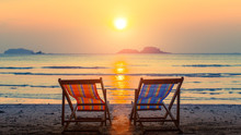 Pair Of Beach Loungers On The Deserted Beach At Sunset.