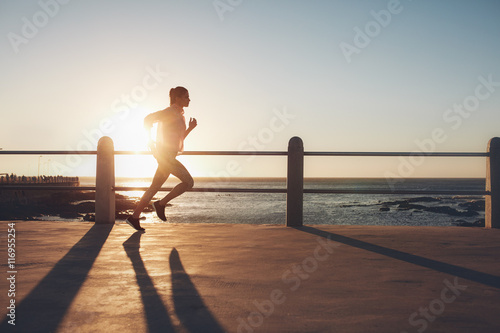 Stickers pour portes Jogging Sportswoman training on seaside promenade at sunset