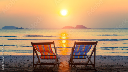 Pair of beach loungers on the deserted beach at sunset. Canvas Print