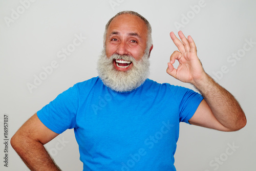 Fotografie, Obraz  Aged man with white beard and broad smile showing OK gesture