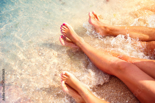 Summer holidays, vacation concept. Family sitting on sandy beach in water