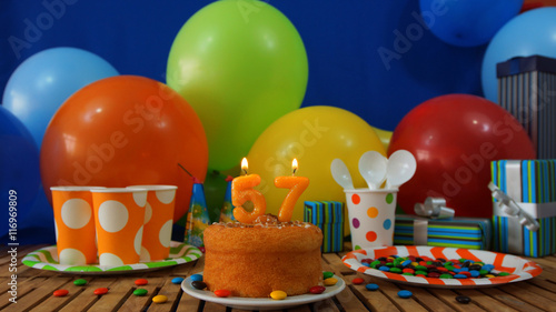 Birthday Cake On Rustic Wooden Table With Background Of Colorful Balloons Gifts Plastic Cups