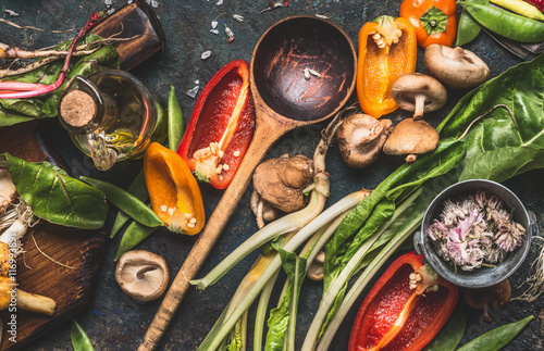 Various fresh vegetables with wooden cooking spoon for healthy eating and nutrition on dark rustic background, top view