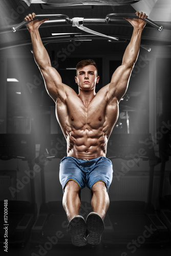 Foto Muscular man working out in gym, doing stomach exercises on a horizontal bar, st