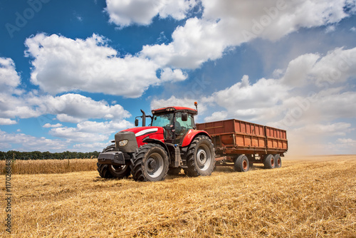 Modern red tractor on the agricultural field on sunny summer day