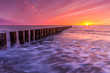Colorful sunset on Batlic sea beach with wooden groyne