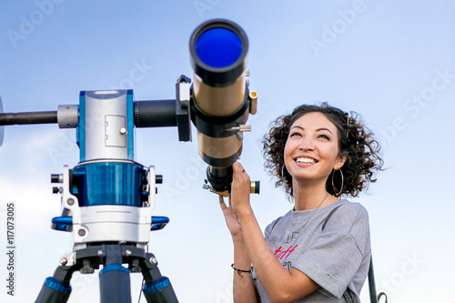 Photo girl looking through a telescope outdoors