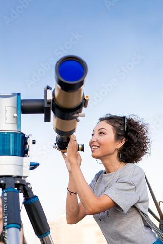 Young smiling woman looking skyward through astronomical telescope Fotobehang