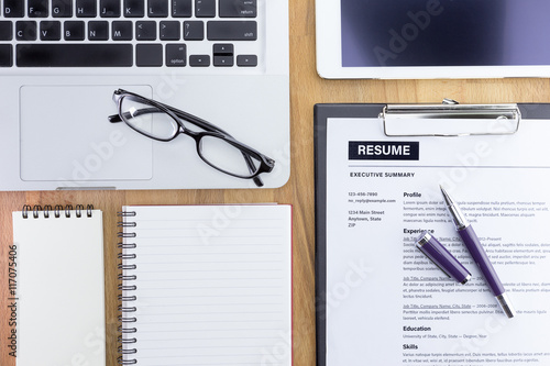 businessman or hr manager review a resume on his desk with magnifier