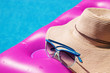Sunglasses and straw hat pink air mattress in swimming pool