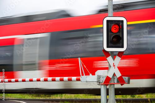 Fotografia, Obraz  An einem Bahnübergang zeigt die Ampel rot und ein Zug fährt vorbei